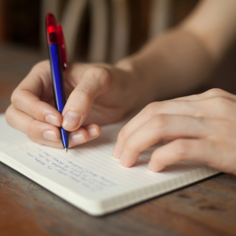 A person writing on a notebook with a blue pen with red cap