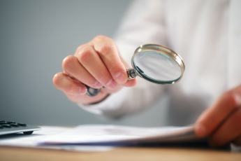 Someone is going through a document carefully with a magnifying glass